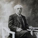 Gammelt foto av Gabriel Fauré som sitter i en stol