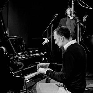 Gunnar Flagstad spiller klaver, mens Frank Havrøy står og synger i bakgrunnen.