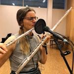 Frida Lereng spiller på to tverrfløyter foran en mikrofon med popfilter.