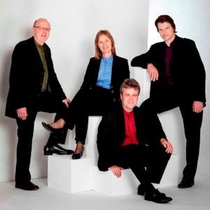 De fire medlemmene av Gothic voices sitter og står i et hvitt rom ikledd svarte dresser og fargerike skjorter.