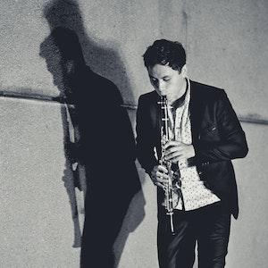 Kenny Keppel spiller på en klarinett foran en betongvegg