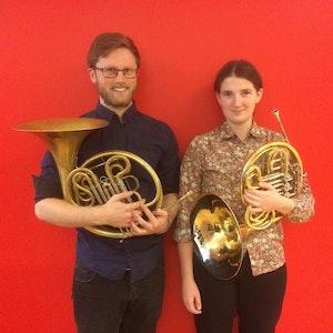 Nora Hannisdal og Nikolai Hauer poserer med hornene sine foran rød bakgrunn