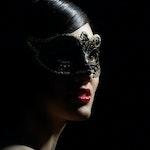 Maskert dame med leppestift i mørket