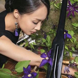 Sanae Yoshida med hånden inni et flygel og blomster rundt