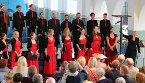 Solistkoret synger i røde og svarte klær