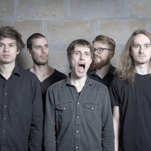 Bandet Yawn står foran murvegg. Et medlem gaper