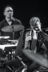 Kalle is playing on the accordion. He is placed on a crowded stage between two drum sets.