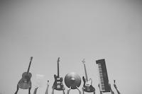 En gitar, en laptop, to mikrofoner, en el-gitar, en el-bass, en cymbal og et keyboard er løftet opp i været.