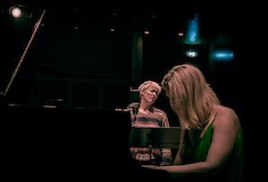 Live Maria Roggen synger foran en mikron og Ingfrid Breie Nyhus spiller konsentrert på en klaver.