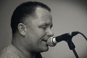 Mann synger følsomt inn i en mikrofon.