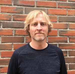 Pål Gustavsen står foran en murvegg og smiler lett til kameraet.