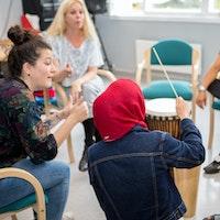 En student sitter i en lyttering og viser hvordan de fem andre skal spille på instrumentene sine.