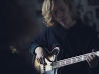 En gutt sitter å spiller på en el-bass.