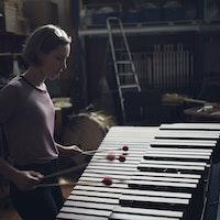 En jente står konsentrert og spiller vibrafon med to køller i hver hånd.