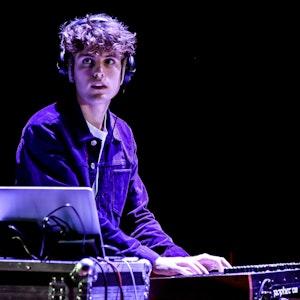 En student står på en scene og spiller på en synth. Han har på headset og ser ned på en datamaskin.
