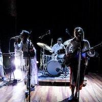 Et band på fem står på scenen og spiller – en på trommer, en på bass, en på gitar, en med dataen som instrument og en som synge.