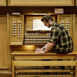 En student sitter foran orgelet i Lindemansalen og skriver noe på et ark.