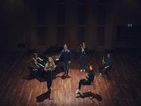 Seks studenter står på scenen i Levinsalen med hvert sitt instrument.