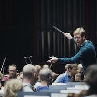 En mann dirigerer et orkester med stor innlevelse.