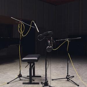Mørkt lydstudio. Opptaksutstyr, pianokrakk, mikrofoner på stativ. Mikrofonene har ledninger i knall gult.