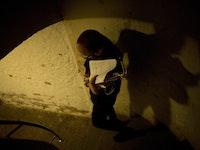 En student går en en vindeltrapp bærende på en saksofon og et noteark