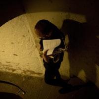 En mann går ned en spiraltrapp omringet av hvit mur, bærende på en saksofon og et noteark.