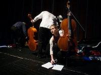 En kvinne og to menn står på en scene med hver sin cello. Kvinner står bøyd over to noteark og de to mennene står med ryggen til.