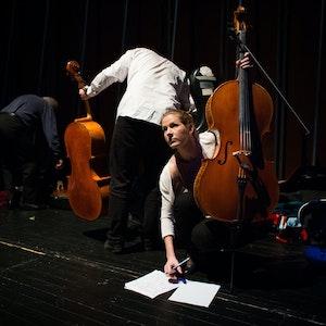 Tre studenter står på en scene, to med celloer og en vendt mot publikum skriblende på noteark.