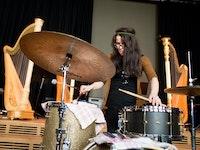 Student sitter og spiller trommer. Bak henne står det fire harper.