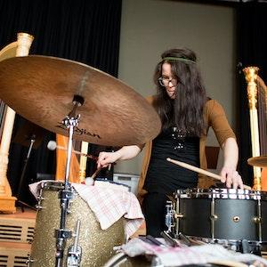 Jente står på en scene og spiller på et trommesett. Bak henne står det tre harper.