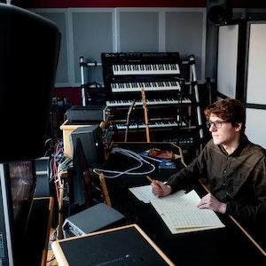 En student befinner seg i et studio proppfull av synther og høyttalere. Han sitter ved en pult og noterer ned noter på et ark.
