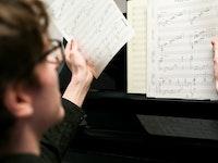 Student sitter ved et piano og blar i noteark