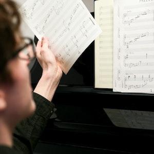 En mann sitter ved et piano og blar i notearkene sine.