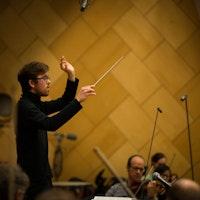 Nils Erik Måseidvåg står foran Kringkastingsorkesteret med begge hendene i været. Den ene hånda holder kan dirigeringspinnen.