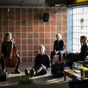 Fem komponiststudenter sitter på gulvet foran en vegg hvor én holder en cello og én taster på en datamaskin. Lys skinner inn gjennom et vindu.