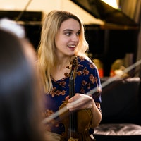 Student står smilende i et flygelrom og holder rundt en fiolin.