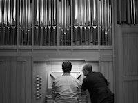 En student spiller på orgelet i Levinsalen. Læreren står ved siden av og peker på notearket.