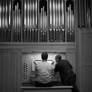 En student og en lærer sitter foran et orgel. Læreren peker på notearket foran studenten.