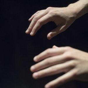 Nærbilde av to hender i et mørkt rom