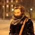 Liv Kristin står ute i skumringen. Bakken er dekket av snø, noe håret og skjerfet til Liv Kristin også er.