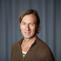Morten står foran en mørk vegg og smiler mot kameraet.